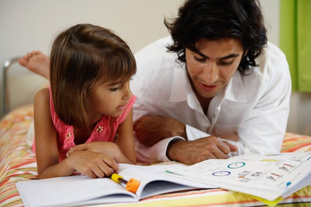 Father helping daughter (8-10) with home-work on bed