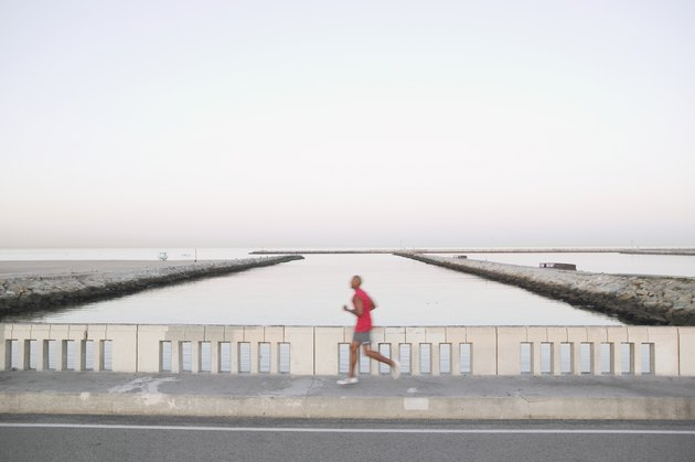 African American male runner on bridge