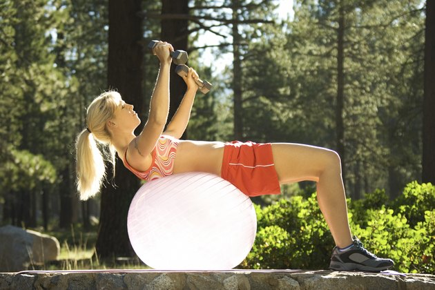 Woman exercising with ball in forest