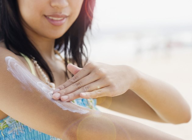 Mid section of woman applying lotion to arm