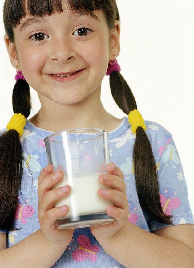 Girl (4-6) holding glass of milk, smiling, portrait