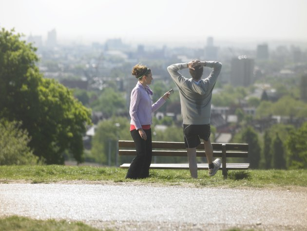 Man and woman resting after exercises, man stretching looking at cityscape, woman holding mobile phone
