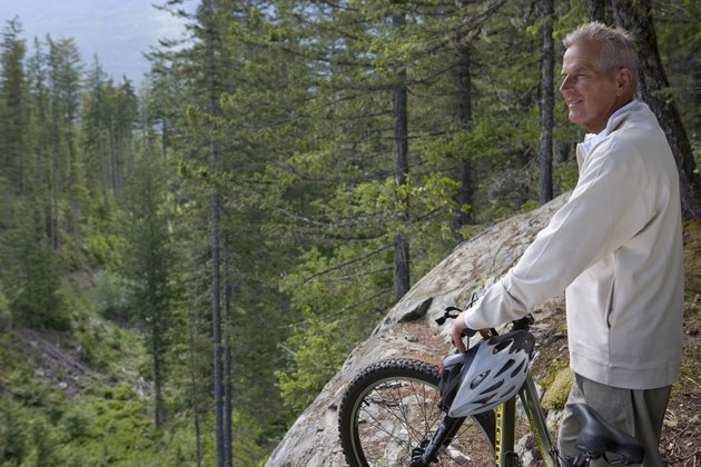 Senior man in mountains standing with bike, looking at view