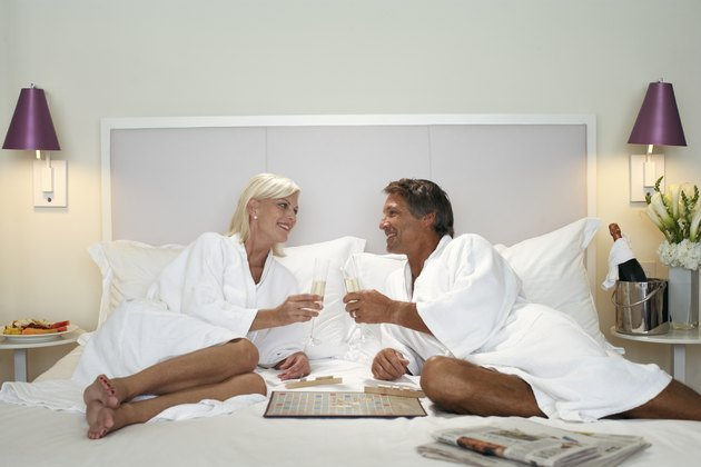 Couple dressed in bathrobes drinking champagne in bed