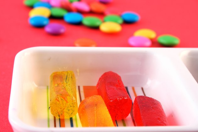 Fruit candies arranged in a tray and few candies scattered in the background