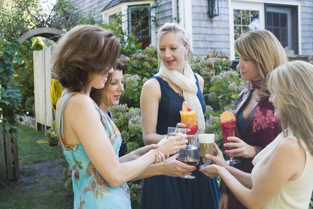 Five women toasting drinks in a garden party