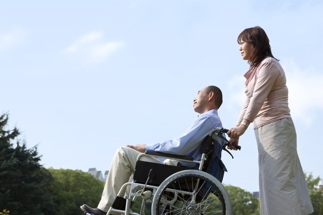 Mature couple in park, woman pushing man in wheelchair, copy space