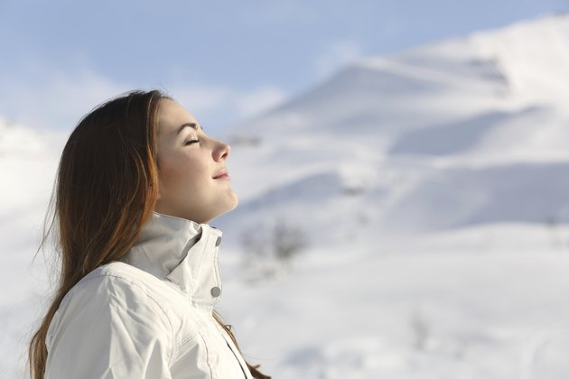 Wman breathing fresh air in winter in a snowy mountain