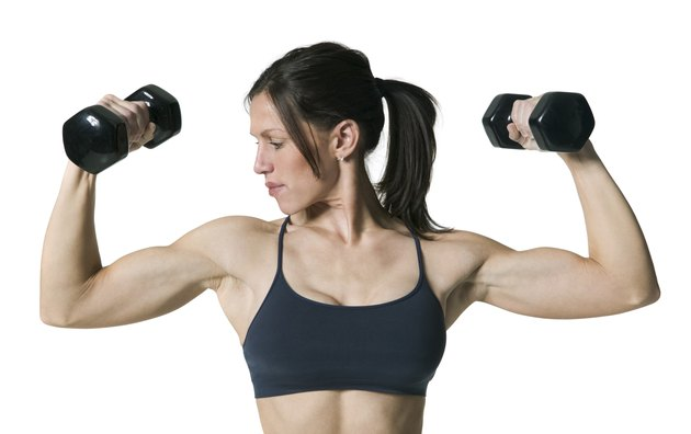 medium shot of an adult woman in a sports bra as she lifts up two dumbbell weights