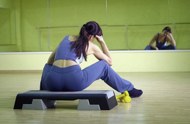 Woman sitting on step in gym resting head on hand, rear view