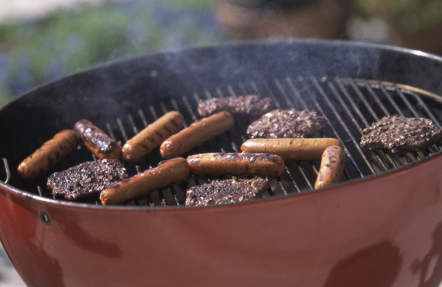 Close-up of hamburgers and hot dogs cooking on a barbecue grill