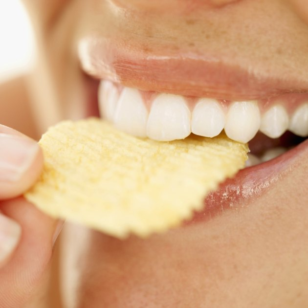 Close-up of a woman biting into a crisp