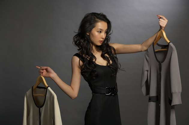 Woman looking at two dresses on hangers