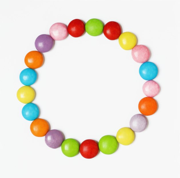 Multi-coloured candies arranged in form of circle on white background, overhead view