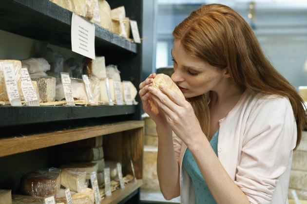 Young woman in shop smelling cheese, close-up