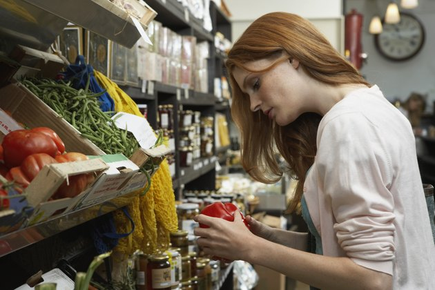 Young woman in shop examining large tomato, side view