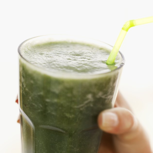 Person holding a glass of thick green vegetable juice