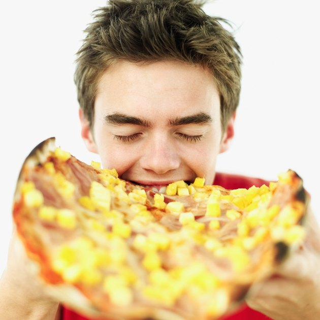 Close-up of a teenage boy (15-17) biting into a whole pizza