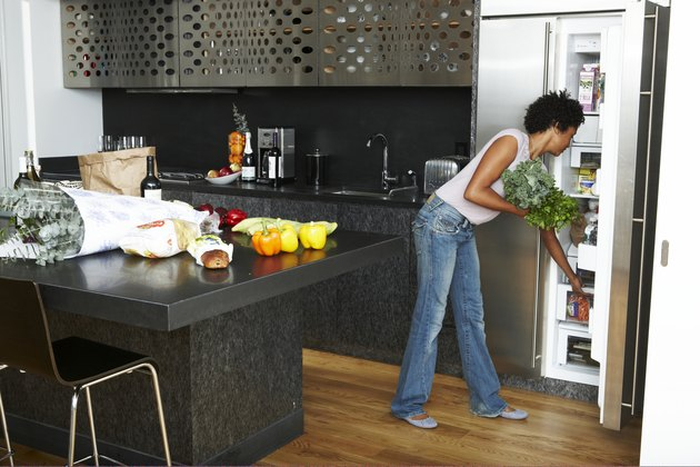 Woman Unpacking groceries in modern kitchen