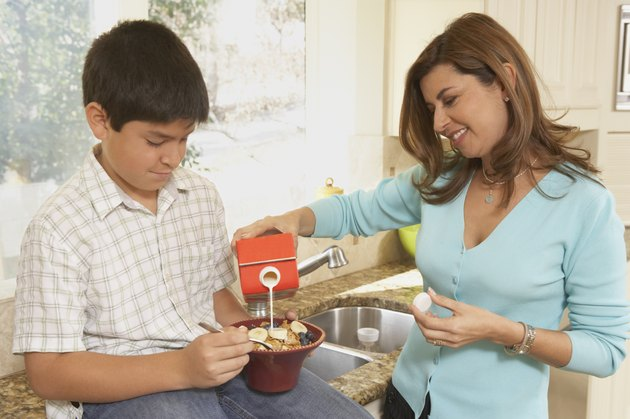 Mother pouring milk into her son's cereal bowl