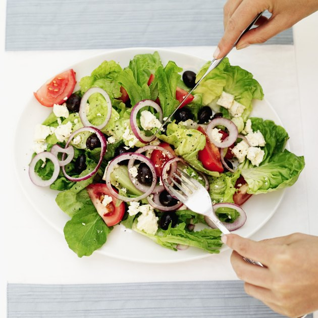 Person tossing salad with a fork and knife