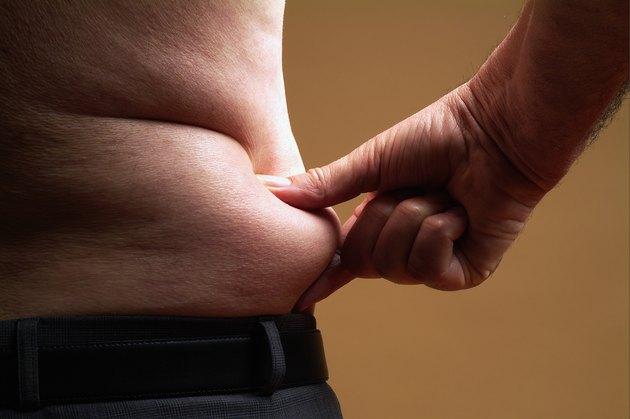 Bare-chested senior man pinching skin around waist, mid section