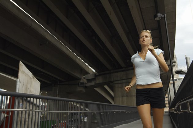 Young woman jogging under fly-over, low angle view