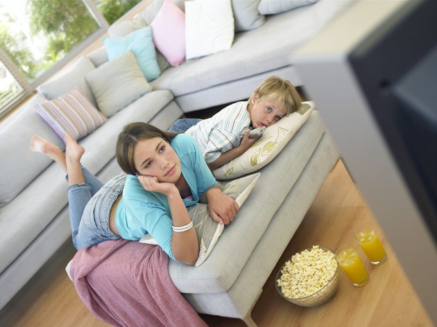 Boy (7-9) and girl (14-16) relaxing in living room watching television