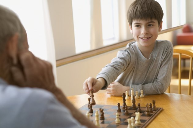 Boy playing chess with elderly man