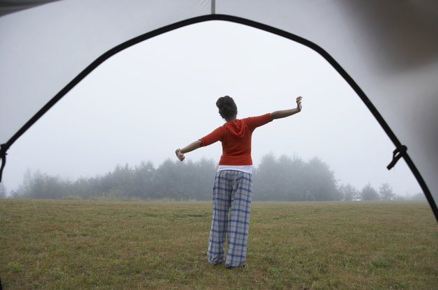 Indian woman in pajamas stretching at campsite