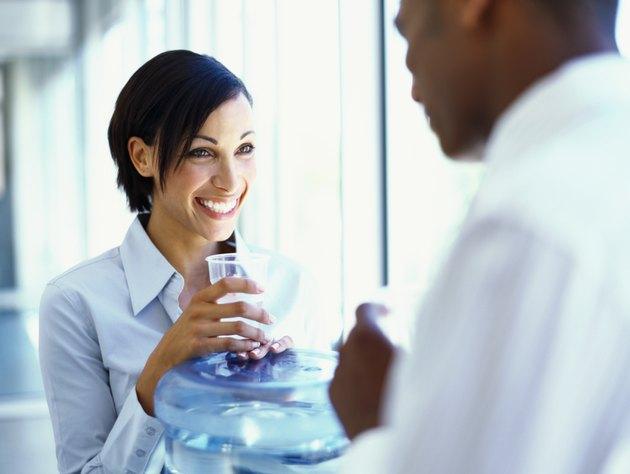 businesswoman and a businessman talking near a water cooler