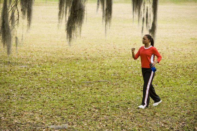 Young woman in sports clothing jogging on ground