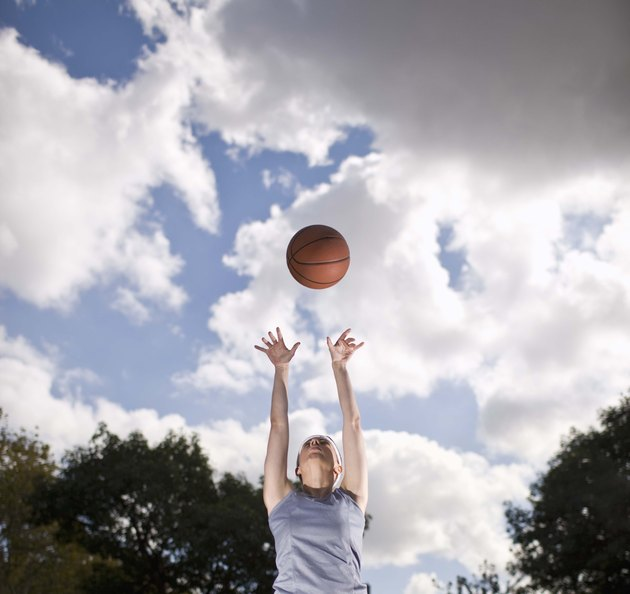 Woman playing basketball outdoors