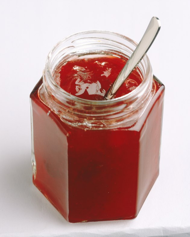 Berry preserved in jar on white background, close-up
