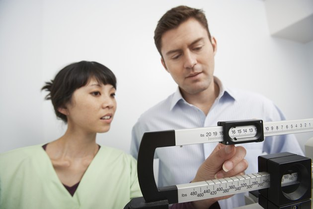 Man standing on weighing scales beside nurse in hospital
