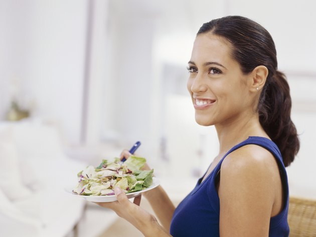 side profile of a young woman holding a plate of salad