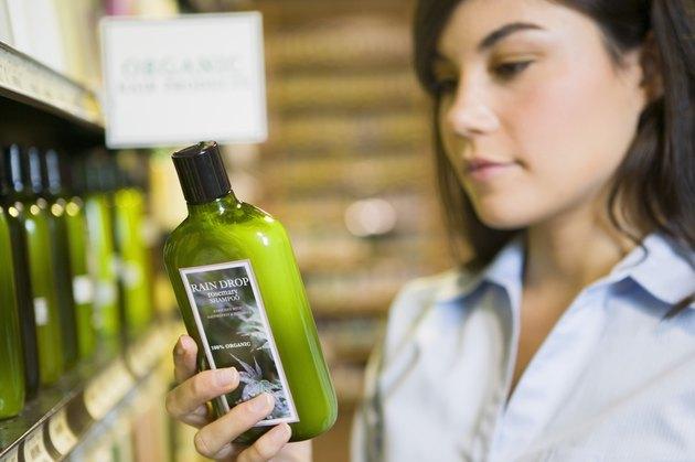 Woman reading label of organic shampoo