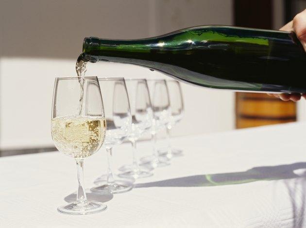 person pouring white wine into a wineglass