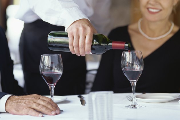 mid section view of a waiter pouring wine into a wineglass