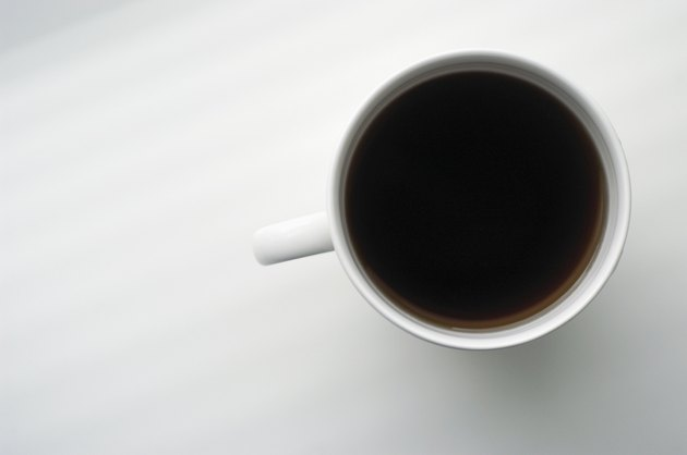 Overhead view of cup of black coffee on white surface