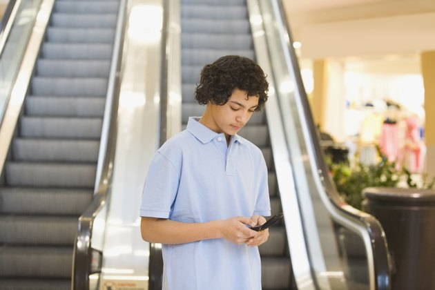 African teenage boy looking at cell phone