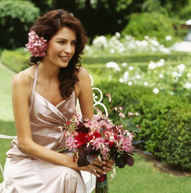 bride sitting on a chair holding bouquet of flowers in a lawn