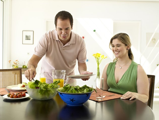 Couple smiling and eating a salad