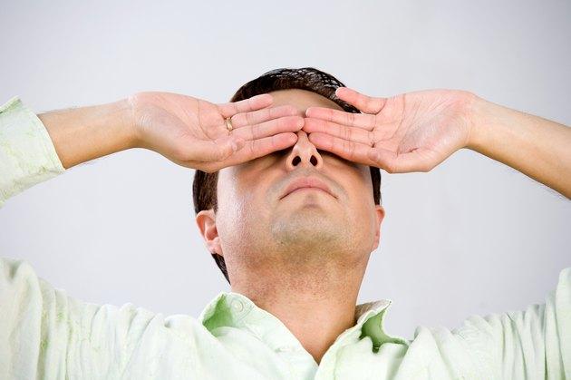 Studio shot of man with hands over eyes