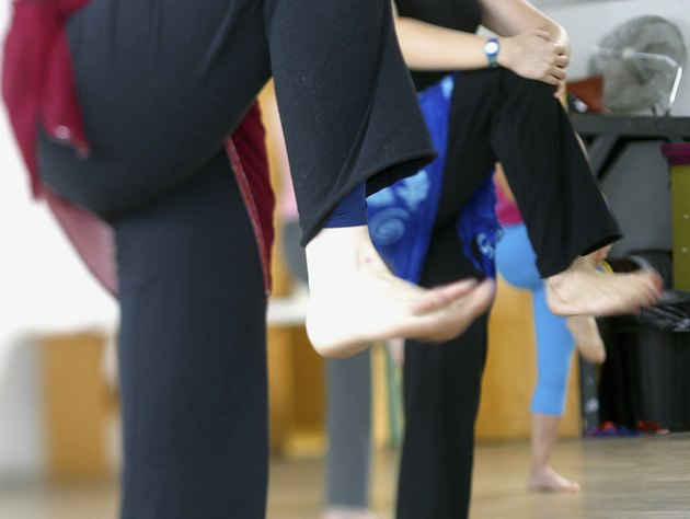 People standing on one leg in a yoga class