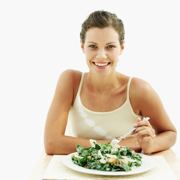 portrait of a young woman sitting with a plate of spinach