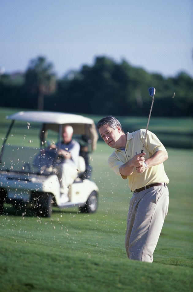 Portrait of a mature man swinging a golf club