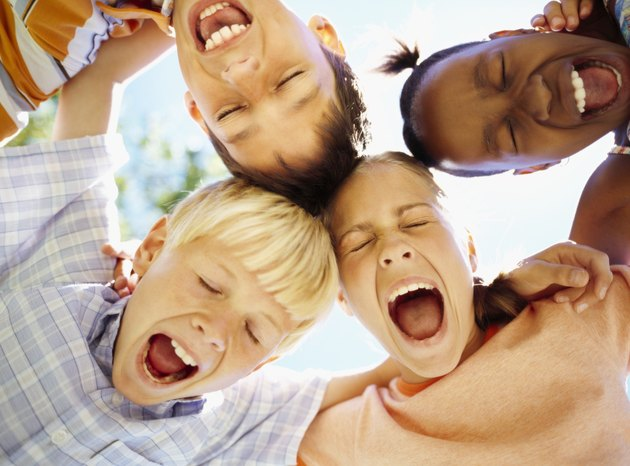 low angle view of children standing in a huddle with their mouth open