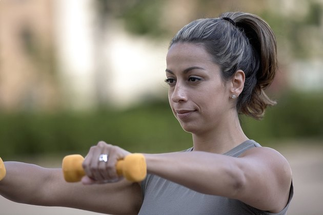 Close-up of a young woman exercising with dumbbells
