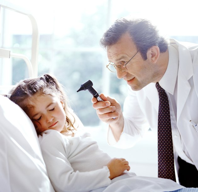 portrait of a male doctor examining a young girls ears with a otoscope